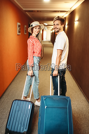 smiling couple with suitcase in hotel