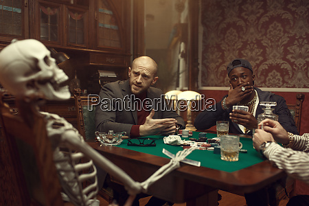 poker players and skeleton at gaming