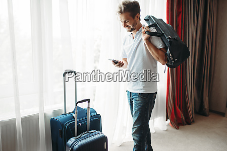 young man with suitcases prepares for