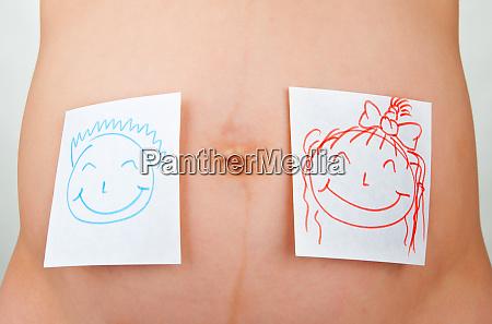 paper stickers on pregnant woman abdomen