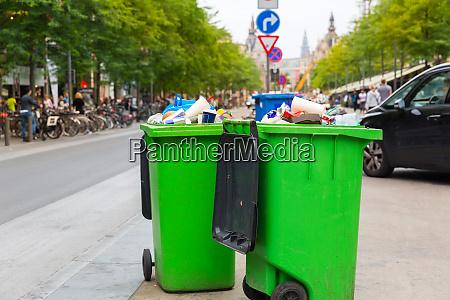 green garbage can on sidewalk european