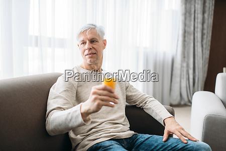 cheerful adult man drinks fresh juice