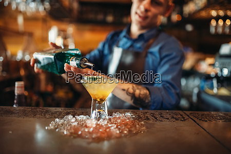 bartender pours beverage into the glass