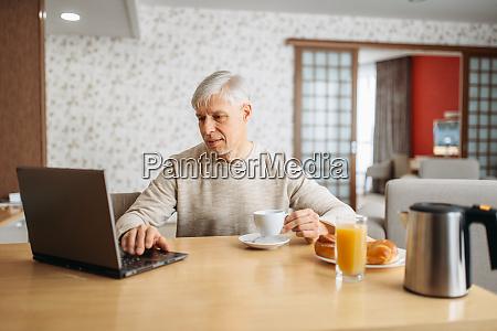 cheerful adult man has breakfast at