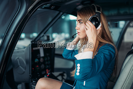 female pilot in headphones in helicopter