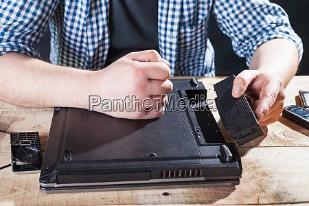 service engineer disassembling broken laptop