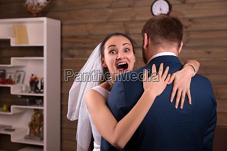 happy bride in veil embracing groom