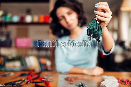 woman shows handmade bracelet needlework hobby