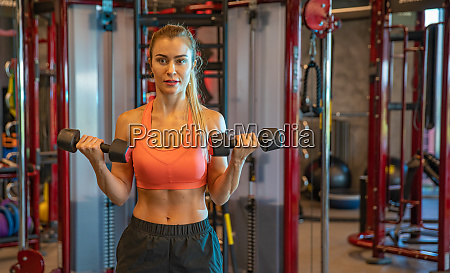 young woman exercising with dumbbells to