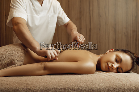 male masseur pampering back to young