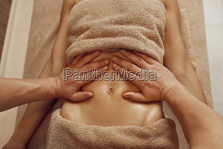 a masseur pampering stomach to young