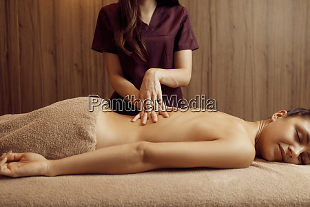 female masseur pampering back to woman