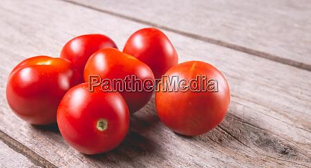 ripe tomatoes on wooden board in