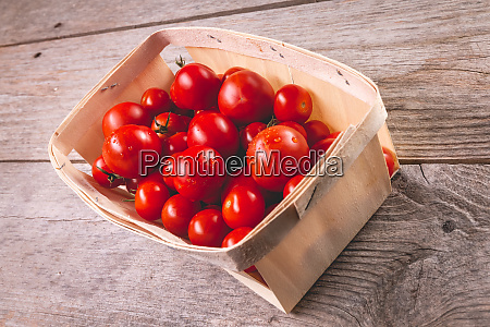 ripe tomatoes in a small wooden