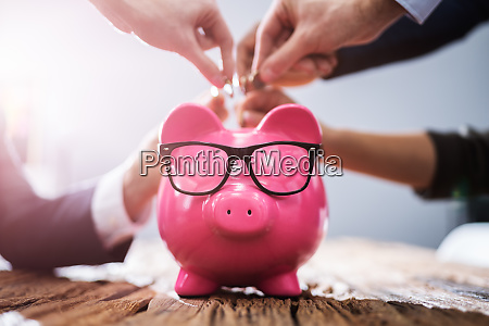 crowdfunding concept people inserting coins into