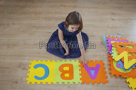 a young girl learning the alphabet