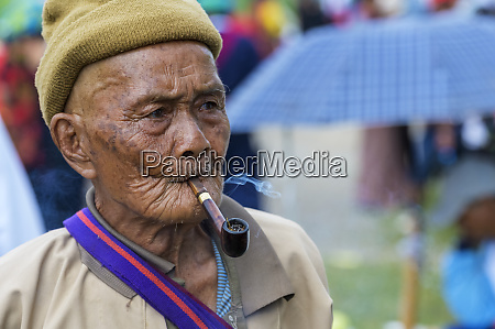 burmese senior man smoking a pipe