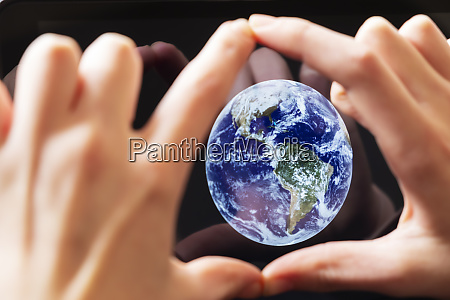 hands framing the earth