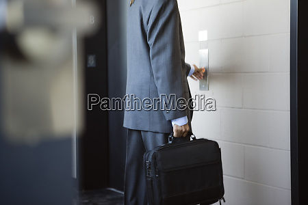a young business man pushing button