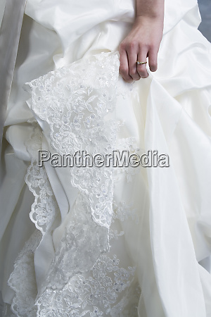 midsection of bride wearing wedding gown