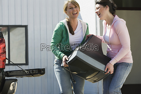 women carrying television