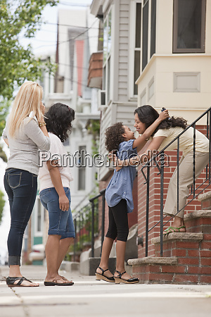 child greets a woman with an