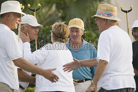 senior people congratulating their friends after