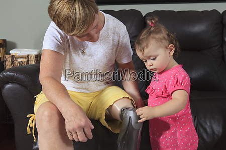 a young girl touches a prosthetic