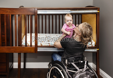 a paraplegic mother lifting a baby