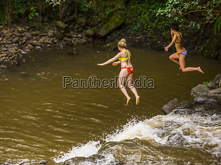 two women wearing bikinis cliff jumping