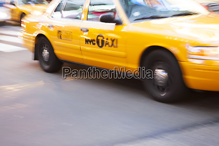 panning image of a yellow taxi