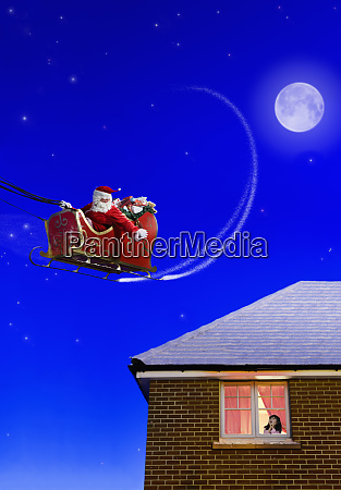 santa clause flying over a house