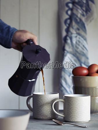 man pouring coffee into mug