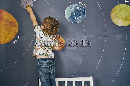 toddler playing with toy on wall