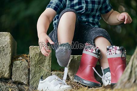toddler removing shoe beside tree