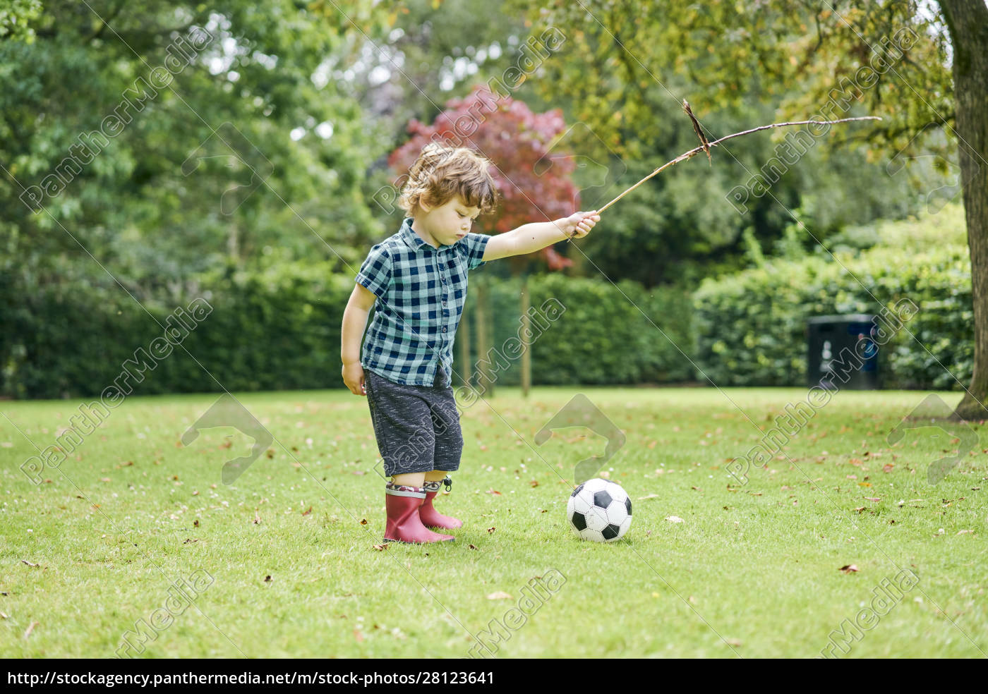 toddler, playing, with, stick, and, football - 28123641