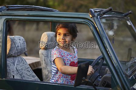 little girl behind wheels of vehicle