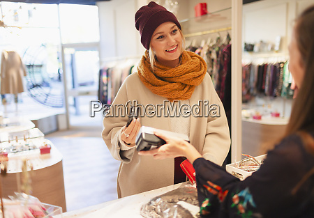 young woman shopping paying with credit