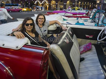 two women sit in the backseat