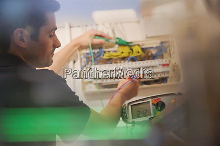 electrician testing fuse box with voltmeter