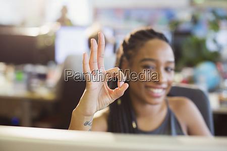 portrait confident ambitious businesswoman gesturing ok