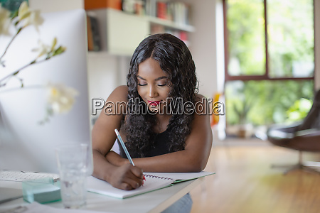 young woman writing in notebook at