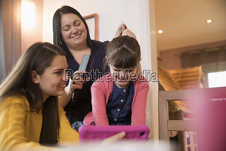 happy mother brushing daughter hair