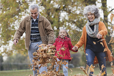 playful grandparents and granddaughter kicking autumn