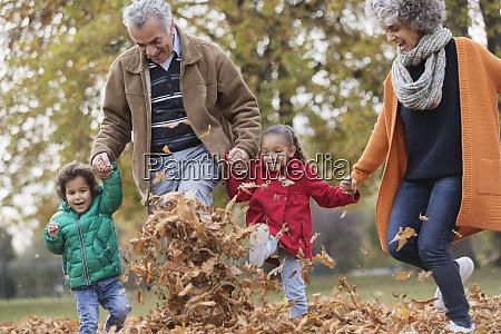 playful grandparents and grandchildren kicking autumn