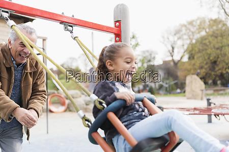 playful grandfather pushing granddaughter on playground