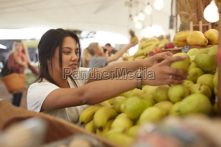 woman working arranging pears at farmers