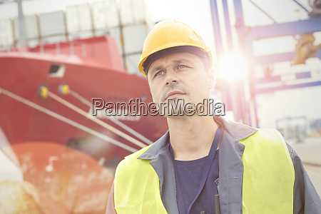 serious dock worker below container ship