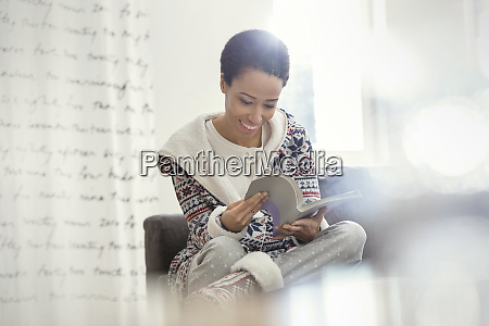 smiling woman in pajamas reading book