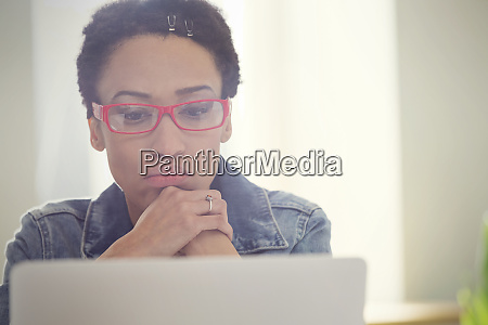 focused woman working at laptop